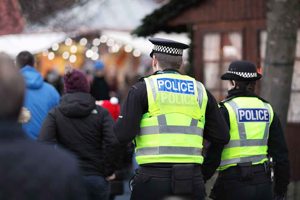 two british police officers in a crowd of people