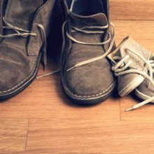 large mans shoes next to small toddler shoes on a wooden floor