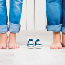 man and woman's feet standing next to empty baby shoes
