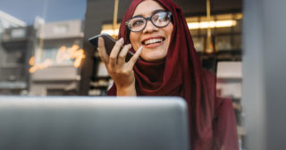 Lady smiling in hijab speaking into a mobile phone