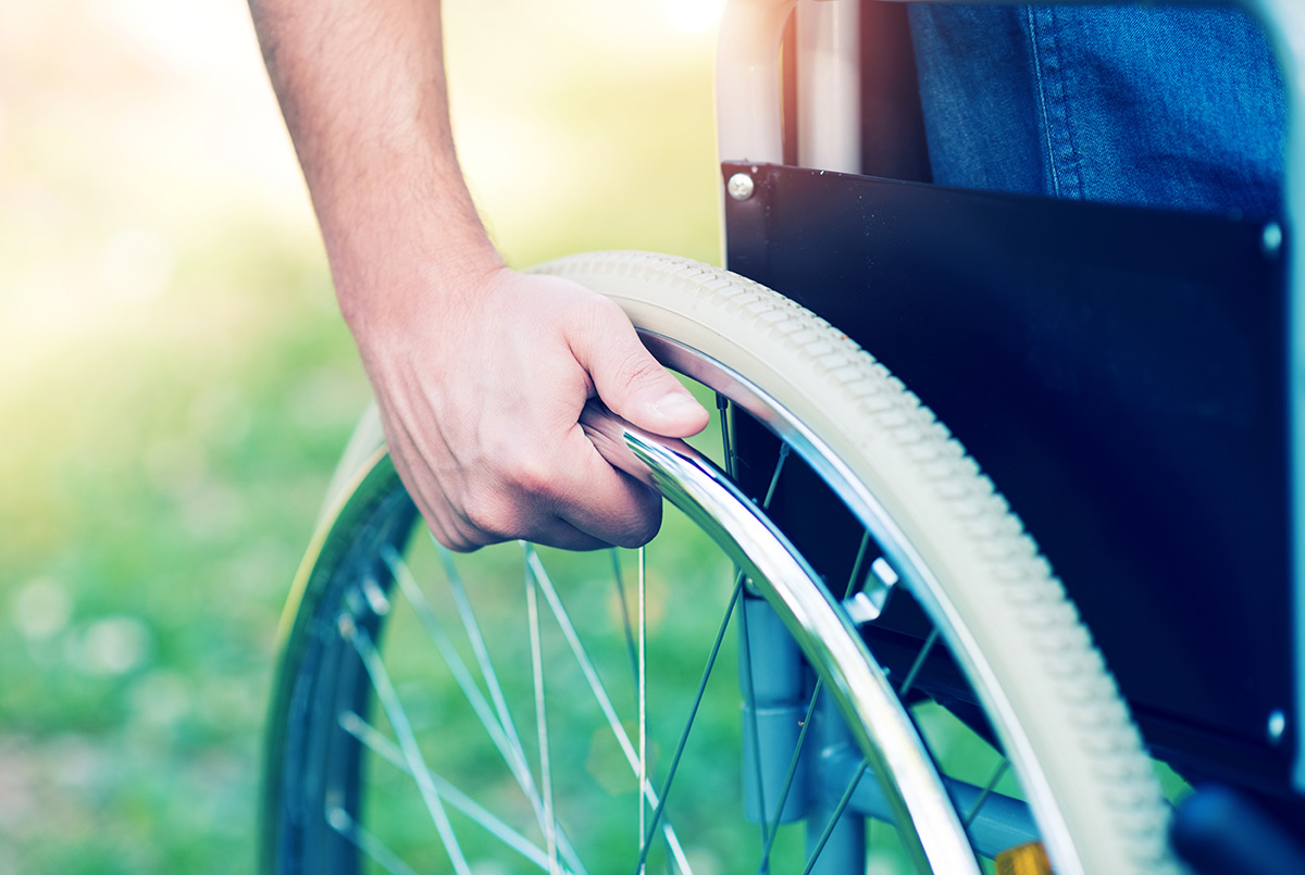 Close up of someone pushing the wheels of a wheelchair