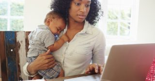 Mother With Baby Working In Office At Home trying to grow her retail business