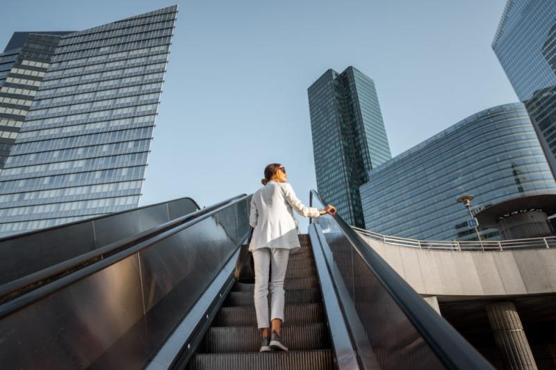 Woman on an escalator with a cityscape ahead of her
