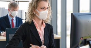 Workers in an office sit far apart and wear face masks for virus avoidance