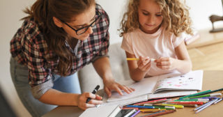 Mum helps daughter with homeschooling at the table