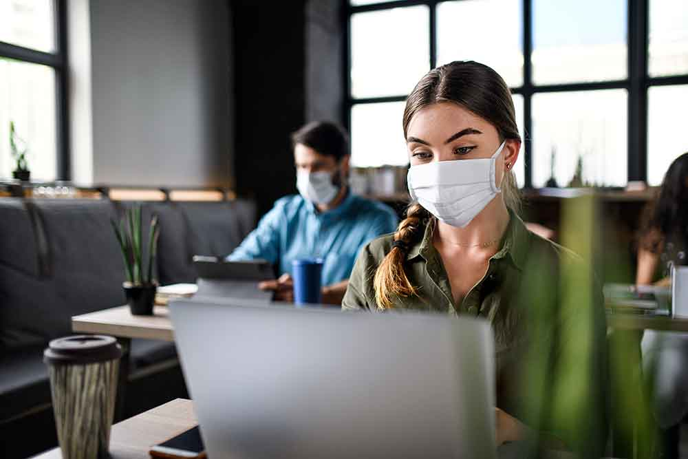 Woman wearing face mask in a work setting with a laptop