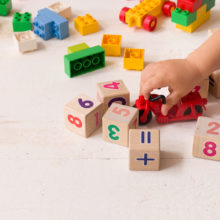 Close up of child's hands playing with colorful plastic bricks and red motocicle at the table. Toddler having fun and building out of bright constructor bricks. Early years childcare